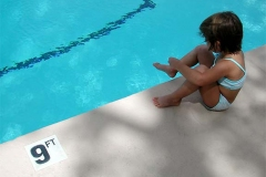 Child sitting on side of swimming pool